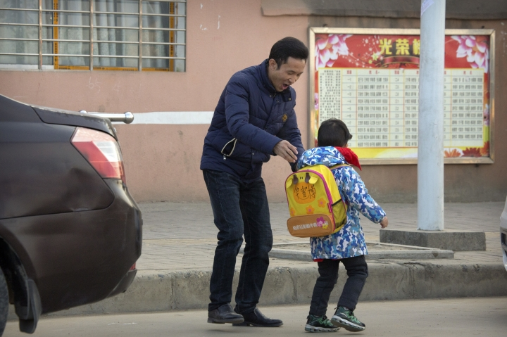 In this Dec. 18, 2017, photo, Chinese labor activist Hua Haifeng, adjusts the backpack of his son Bo Bo, 4, as he takes him to school on the outskirts of Xiangyang in central China's Hubei Province. Apple Inc. and Ivanka Trump's brand both rely on Chinese suppliers that have been criticized for workplace abuses. But they've taken contrasting approaches to dealing with supply chain problems. When Apple learned thousands of student workers at an iPhone supplier had been underpaid, it helped them get their money back. After three men investigating labor abuses at factories that made Ivanka Trump shoes were arrested last year, neither Ivanka Trump nor her brand spoke out. (AP Photo/Mark Schiefelbein)