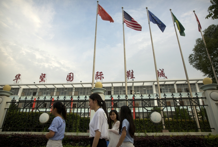 FILE - In this June 6, 2017, file photo, Chinese, American, and other international flags fly as women walk past a Huajian Group shoe factory, which made shoes for Ivanka Trump's brand, in Ganzhou in southern China's Jiangxi Province. Apple Inc. and Ivanka Trump's brand both rely on Chinese suppliers that have been criticized for workplace abuses. But they've taken contrasting approaches to dealing with supply chain problems. When Apple learned thousands of student workers at an iPhone supplier had been underpaid, it helped them get their money back. After three men investigating labor abuses at factories that made Ivanka Trump shoes were arrested last year, neither Ivanka Trump nor her brand spoke out. (AP Photo/Mark Schiefelbein, File)