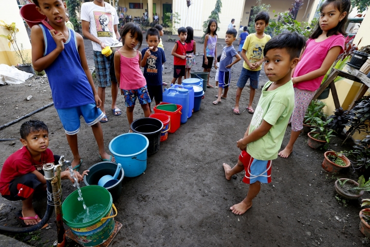 Children line up to collect water at an evacuation center in Miisi village, Ligao township, following the sporadic eruptions of Mayon volcano, Friday, Jan. 26, 2018, in Albay province, around 200 miles (340 kilometers) southeast of Manila, Philippines. (AP Photo/Bullit Marquez)