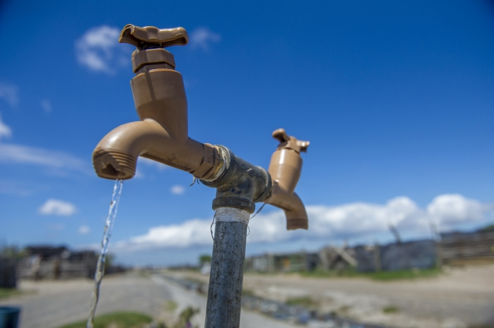 """A communal tap runs as people collect water in an informal settlement near Cape Town, South Africa, Tuesday, Jan. 23, 2018. While the city urges people to restrict water usage, many living in poor areas already have limited access to water, and the day that the city runs out of water, ominously known as """"Day Zero"""", moves ever closer for the nearly 4 million residents. (AP Photo)"""
