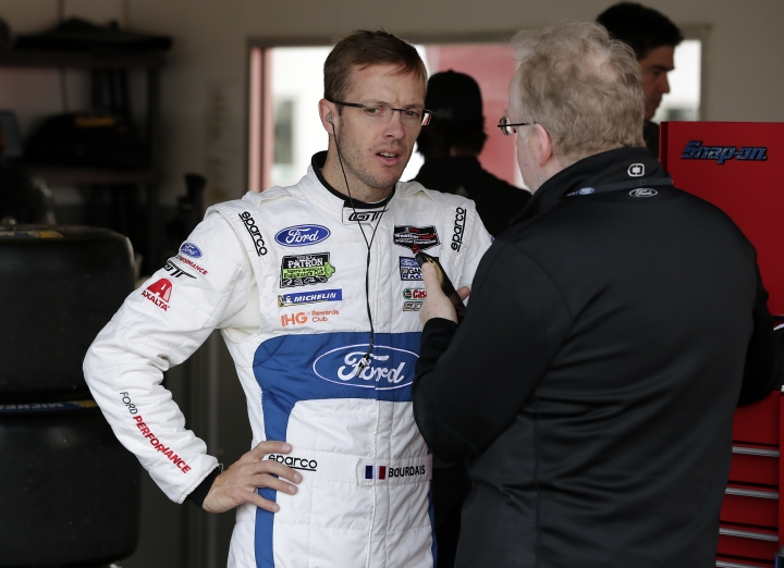 Sebastien Bourdais, of France, talks with a reporter in his garage during a practice session for the IMSA 24-hour auto race at Daytona International Speedway, Friday, Jan. 26, 2018, in Daytona Beach, Fla. (AP Photo/John Raoux)
