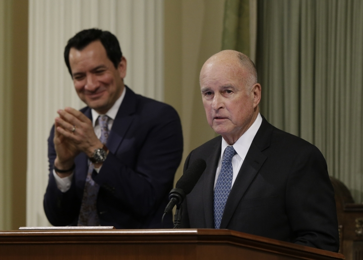 In this photo taken Thursday, Jan. 25, 2018, California Gov. Jerry Brown, right, receives applause from Assembly Speaker Anthony Rendon, of Lakewood, after delivering his annual State of the State address in Sacramento, Calif. Brown called for putting 5 million zero-emission vehicles on the road by 2030 in his speech and on Friday issued an executive order and called for a $2.5 billion investment to help reach that goal. (AP Photo/Rich Pedroncelli)