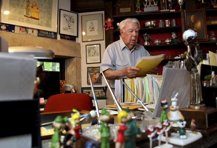 FILE - In this Aug. 16, 2010 file photo, Mort Walker, the artist and author of the Beetle Bailey comic strip, looks over notes and documents in his studio in Stamford, Conn. On Saturday, Jan. 27, 2018, a family member said the comic strip artist has died. He was 94. (AP Photo/Craig Ruttle)