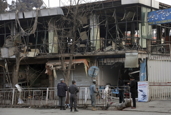 """Members of Afghan security forces stand guard at the site of Saturday's suicide attack in Kabul, Afghanistan, Sunday, Jan. 28, 2018. U.S. President Donald Trump is condemning """"the despicable car bombing attack"""" in the Afghan capital of Kabul. (AP Photo/Rahmat Gul)"""