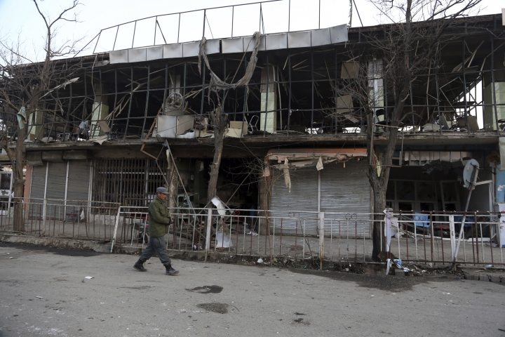 "A member of Afghan security forces walks past the site of Saturday's suicide attack in Kabul, Afghanistan, Sunday, Jan. 28, 2018. President Donald Trump is condemning ""the despicable car bombing attack"" in the Afghan capital of Kabul. (AP Photo/Rahmat Gul)"