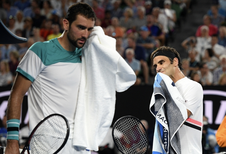 Switzerland's Roger Federer, right, walks past Croatia's Marin Cilic during a change of ends in the men's singles final at the Australian Open tennis championships in Melbourne, Australia, Sunday, Jan. 28, 2018. (AP Photo/Andy Brownbill)
