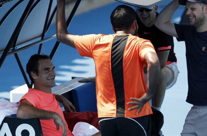 Switzerland's Roger Federer smiles as he talks with his team during a practice session at the Australian Open tennis championships in Melbourne, Australia, Saturday, Jan. 27, 2018. Federer will play Croatia's Marin Cilic in the men's singles final on Sunday, Jan. 28, 2018. (AP Photo/Ng Han Guan)