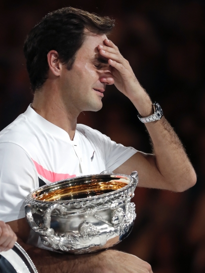 Switzerland's Roger Federer wipes tears from his eyes as he holds his trophy after defeating Croatia's Marin Cilic during the men's singles final at the Australian Open tennis championships in Melbourne, Australia, Sunday, Jan. 28, 2018. (AP Photo/Vincent Thian)