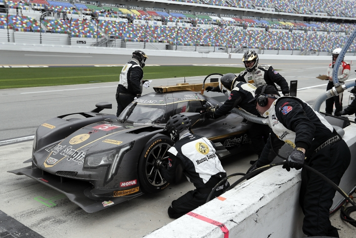 Filipe Albuquerque, of Portugal, sits behind the wheel as crew members change tires and add fuel to the Cadillac DPi during a pit stop in the IMSA 24-hour auto race at Daytona International Speedway, Sunday, Jan. 28, 2018, in Daytona Beach, Fla. (AP Photo/John Raoux)