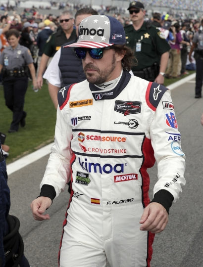 Fernando Alonso, of Spain, walks down pit road to his car before the start of the IMSA 24-hour auto race at Daytona International Speedway, Saturday, Jan. 27, 2018, in Daytona Beach, Fla. (AP Photo/John Raoux)