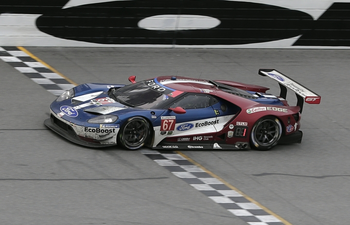 Ryan Briscoe, of Australia, crosses the finish line in a Ford GT to win the GT Le Mans class of the IMSA 24-hour auto race at Daytona International Speedway, Sunday, Jan. 28, 2018, in Daytona Beach, Fla. (AP Photo/John Raoux)