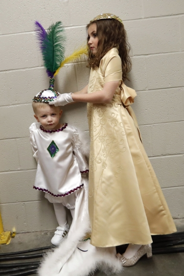 A member of the royal court adjusts the hat of Cason Stephens, 2, which kept coming off, backstage before the start of the Little Rascals Mardi Gras Ball in Kenner, La., Thursday, Jan. 25, 2018. The largest of the Mardi Gras kid parades is Little Rascals, and the Little Rascals ball is the only formal ball children are allowed to attend. (AP Photo/Gerald Herbert)