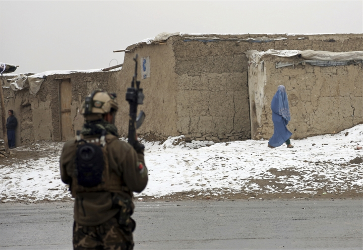 An Afghan woman leaves the site of an attack at the Marshal Fahim academy in Kabul, Afghanistan Monday, Jan. 29, 2018. Islamic State militants attacked Afghan soldiers guarding the military academy in the capital Kabul on Monday, killing at least 10 troops and wounding 16. AP Photo/Rahmat Gul)