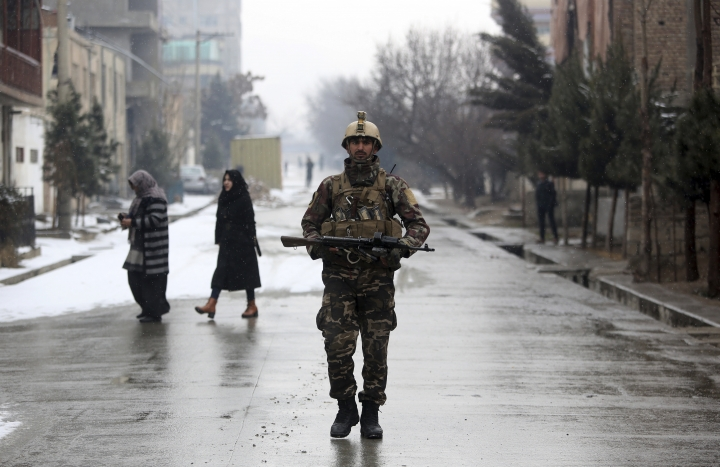 An Afghan security personnel walks at the site of an attack at the Marshal Fahim academy in Kabul, Afghanistan Monday, Jan. 29, 2018. Insurgents attacked an Afghan army unit guarding a military academy in the capital of Kabul on Monday, killing at least five soldiers and wounding 10, officials said. (AP Photo/Rahmat Gul)