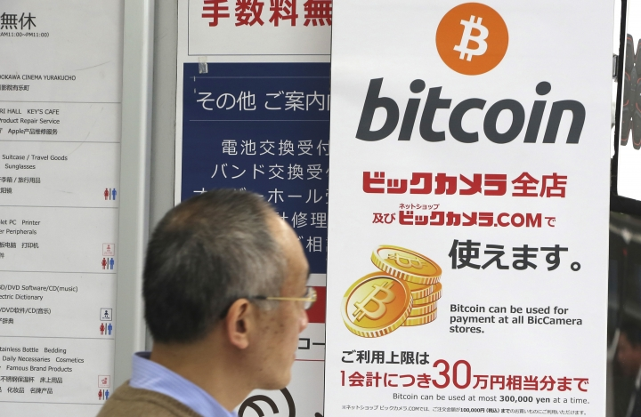 In this Friday, Jan. 19, 2018, photo, a man walks past a poster of bitcoin displayed at a retail store in Tokyo. Blockchain is a decentralized technology that can make transactions safe and secure, but crypto-currency exchanges that trade bitcoins and other virtual currencies that are based on this technology have been hacked because they are not working on secure networks. (AP Photo/Koji Sasahara)