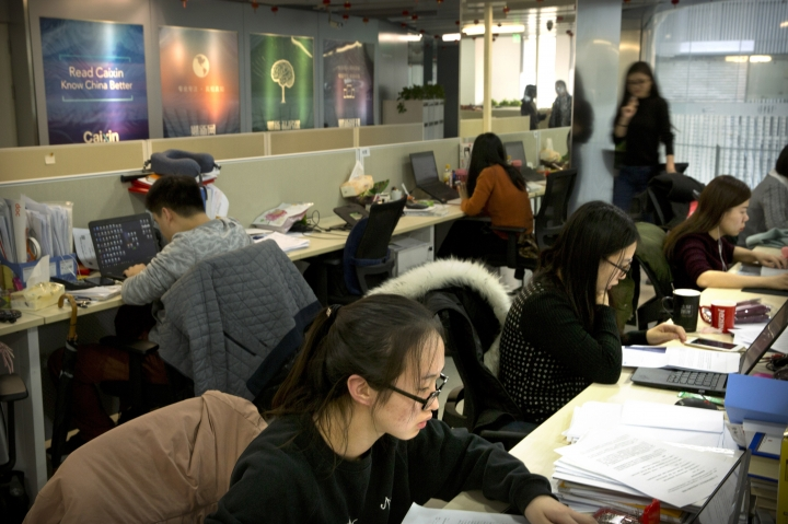 "In this Jan. 18, 2018 photo, staffers work at the Caixin Media offices in Beijing. In a rare interview with the Associated Press, publisher Hu Shuli spoke bullishly about transitioning into a publisher role at Caixin, the newsmagazine she co-founded in 2009, and the prospect of doing more to help Chinese women gain their rights as the ""Me Too"" movement goes global. (AP Photo/Mark Schiefelbein)"