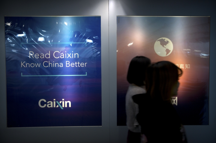 """In this Jan. 18, 2018 photo, staffers walk past a billboard reading """"Read Caixin - Know China Better"""" at the Caixin Media offices in Beijing. In a rare interview with the Associated Press, publisher Hu Shuli spoke bullishly about transitioning into a publisher role at Caixin, the newsmagazine she co-founded in 2009, and the prospect of doing more to help Chinese women gain their rights as the """"Me Too"""" movement goes global. (AP Photo/Mark Schiefelbein)"""