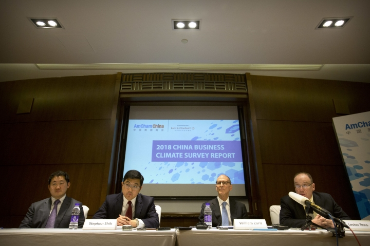 "From left; Yin Chen and Stephen Shih of Bain and Company and William Zarit and Lester Ross of the American Chamber of Commerce in China listen to a reporter's question during a press conference to unveil the group's 2018 China Business Climate Survey Report in Beijing, Tuesday, Jan. 30, 2018. The head of an American business group says Chinese officials have warned ""there will be retaliation"" if President Donald Trump launches trade remedies in disputes over technology, steel and other issues. (AP Photo/Mark Schiefelbein)"