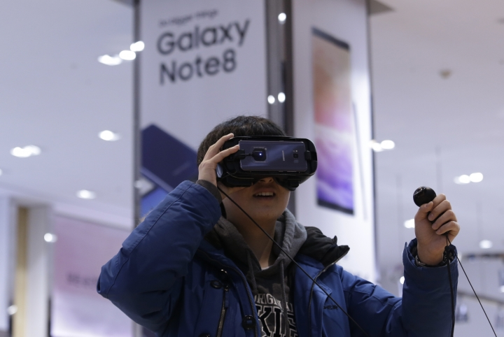 An elementary school student wears a Samsung Electronics' Gear VR at its shop in Seoul, South Korea, Wednesday, Jan. 31, 2018. Samsung Electronics has reported a surge in quarterly earnings thanks to its record-breaking chip business. (AP Photo/Ahn Young-joon)