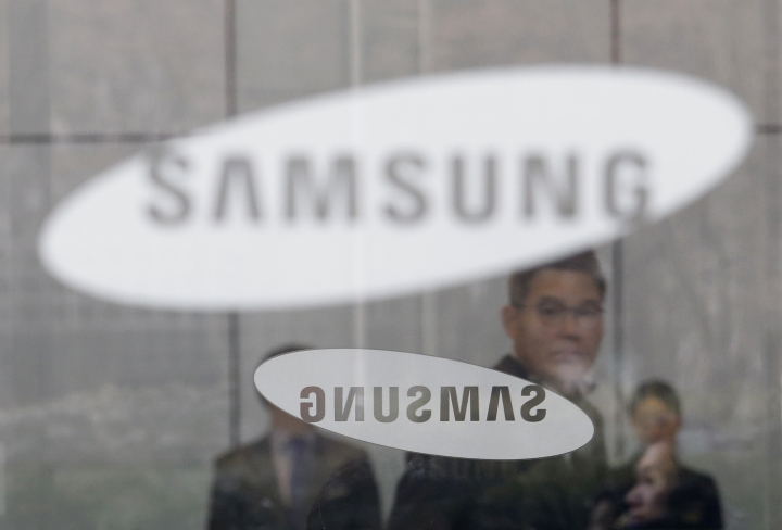 An employee walks past logos of the Samsung Electronics Co. at its office in Seoul, South Korea, Wednesday, Jan. 31, 2018. Samsung Electronics has reported a surge in quarterly earnings thanks to its record-breaking chip business. (AP Photo/Ahn Young-joon)
