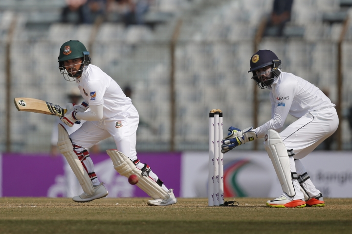 Bangladesh's Mominul Haque, left, plays a shot, as Sri Lanka's wicketkeeper Niroshan Dickwella watches during the first day of their first test cricket match in Chittagong, Bangladesh, Wednesday, Jan. 31, 2018. (AP Photo/A.M. Ahad)