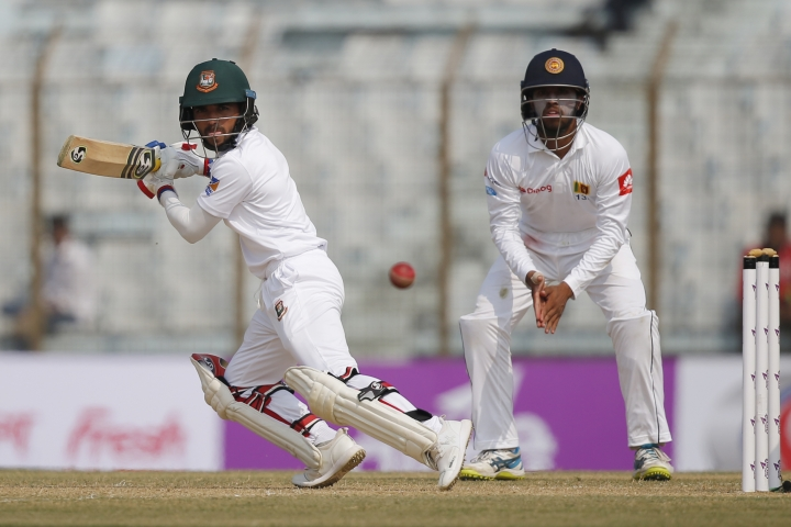 Bangladesh's Mominul Haque, left, plays a shot, as Sri Lanka's Kusal Perera watches during the first day of their first test cricket match in Chittagong, Bangladesh, Wednesday, Jan. 31, 2018. (AP Photo/A.M. Ahad)