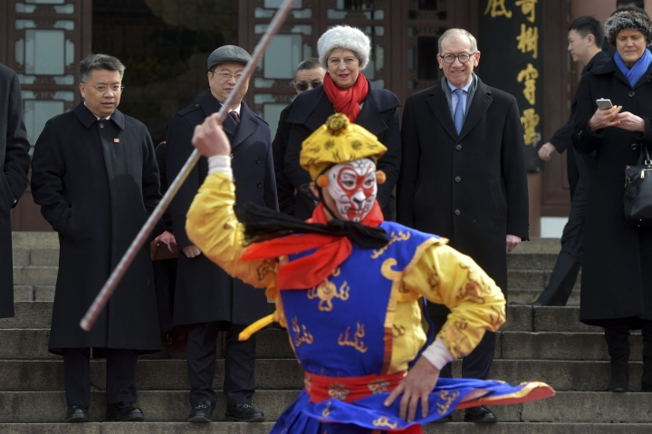 British Prime Minister Theresa May and her husband Philip May, right, accompanied by Chen Yixin, the Communist Party leader of Wuhan, second from left, watch an outdoor opera show during a tour to the ancient Huanghelou Tower in Wuhan in central China's Hubei province, Wednesday, Jan. 31, 2018. (Chinatopix via AP)