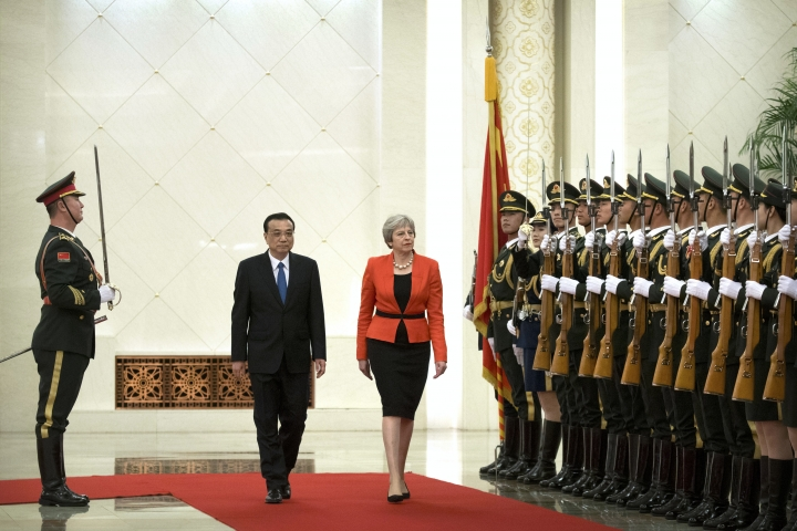 Chinese Premier Li Keqiang, second from left, and British Prime Minister Theresa May review a Chinese honor guard during a welcome ceremony at the Great Hall of the People in Beijing, Wednesday, Jan. 31, 2018. (AP Photo/Mark Schiefelbein)