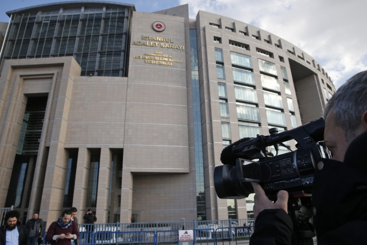A news cameraman films outside a court in Istanbul, Wednesday, Jan. 31, 2018. Turkey's state-run news agency Anadolu Agency says the court has sentenced three people to life prison terms for their involvement in an Islamic State group suicide bomb attack in Jan. 2016 at Istanbul's historic Sultanahmet district that killed 12 German tourists and wounded 15 people, including nine Germans and citizens of Norway, Peru and South Korea. (AP Photo/Lefteris Pitarakis)