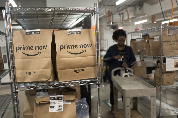 In this Dec. 20, 2017, photo, Prime Now customer orders are ready for delivery at the Amazon warehouse, in New York. Details on the new health care company Amazon announced on Tuesday, Jan. 30, 2018, with Berkshire and JPMorgan are slim. But experts say Amazon has the ability to shake up the industry. (AP Photo/Mark Lennihan)