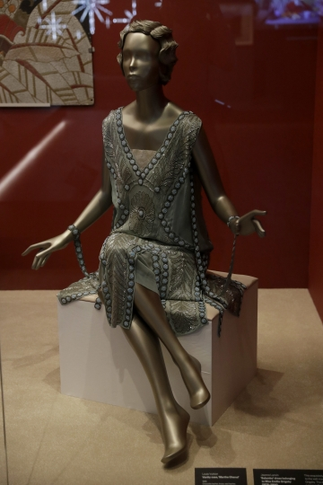"""A 1925 Jeanne Lanvin """"Salambo"""" beaded flapper dress that belonged to the wealthy American adventuress Emilie Grigsby is displayed behind glass during a media preview of the """"Ocean Liners: Speed and Style"""" exhibition at the V&A gallery in London, Wednesday, Jan. 31, 2018. The exhibition, jointly organised by the Peabody Essex Museum in Salem, Massachusetts and the V&A, studies the design and cultural impacts of ocean liners. It features over 250 objects, and opens to the public from Feb. 3 until June 17. (AP Photo/Matt Dunham)"""