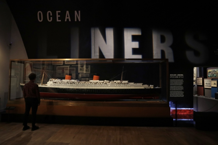 "A staff member poses for photographs next to an around 1938 model of the Queen Elizabeth ocean liner made by Bassett-Lowke during a media preview of the ""Ocean Liners: Speed and Style"" exhibition at the V&A gallery in London, Wednesday, Jan. 31, 2018. The exhibition, jointly organised by the Peabody Essex Museum in Salem, Massachusetts and the V&A, studies the design and cultural impacts of ocean liners. It features over 250 objects, and opens to the public from Feb. 3 until June 17. (AP Photo/Matt Dunham)"