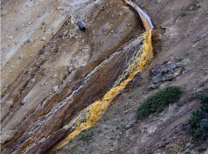FILE--In this Aug. 13, 2015, file photo, wastewater flows from a trough and down a steep ravine at the site of the blowout at the Gold King mine which triggered a major spill of toxic wastewater, outside Silverton, Colo.Crumbling mine tunnels awash with polluted waters perforate the Colorado mountains, and scientists may one day send robots creeping through the pitch-black passages to study the mysterious currents that sometimes burst to the surface with devastating effects. (AP Photo/Brennan Linsley)