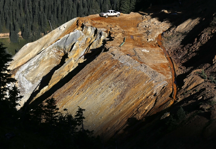 FILE - In this Aug. 13, 2015 file photo, wastewater flows down a trough, right, from the site of the blowout at the Gold King mine which triggered a major spill of toxic wastewater, outside Silverton, Colo. Crumbling mine tunnels awash with polluted waters perforate the Colorado mountains, and scientists may one day send robots creeping through the pitch-black passages to study the mysterious currents that sometimes burst to the surface with devastating effects. (AP Photo/Brennan Linsley, file)