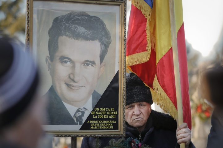 "FILE - In this Friday, Jan. 26, 2018, file photo, a man holds a Romanian flag next to the official portrait of Romanian communist dictator Nicolae Ceausescu, placed next to his grave, as communism nostalgics gather to mark 100 years since he was born, in Bucharest, Romania. A Romanian auction house is selling memorabilia that belonged to Ceausescu to mark what would have been his 100th birthday. Text on portrait reads ""A man like him is only born every 500 years"" (AP Photo/Vadim Ghirda, File)"
