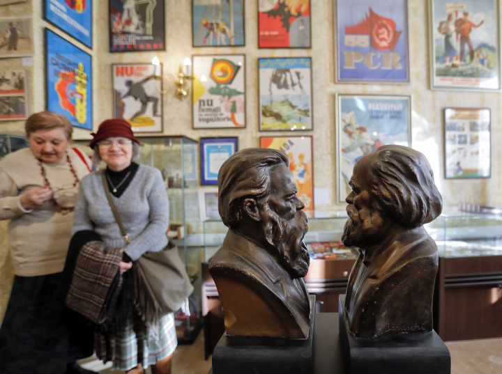 In this photo taken on Tuesday, Jan. 30, 2018, visitors look at busts of Friedrich Engels, left, and Karl Marx, on display at an auction house in Bucharest, Romania. A Romanian auction house is selling memorabilia that belonged to former Communist dictator Nicolae Ceausescu to mark what would have been his 100th birthday. (AP Photo/Vadim Ghirda)