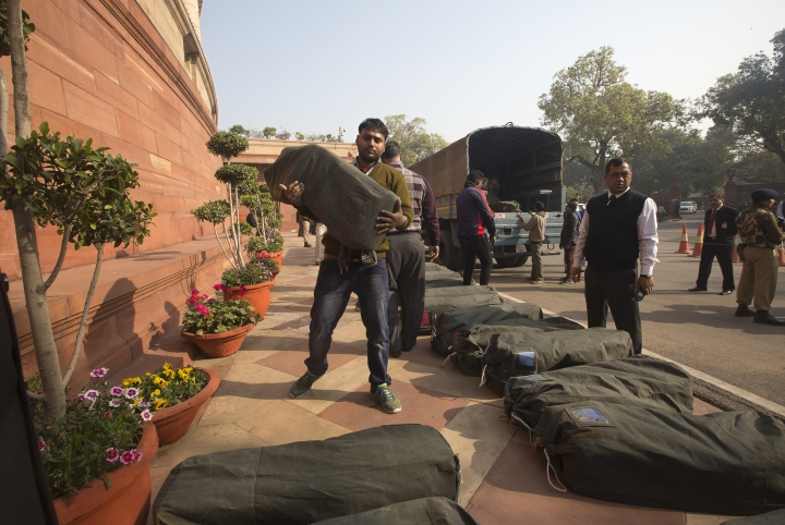 An Indian worker carries a bag containing the copies of the federal budget for the year 2018-19, that will be distributed to lawmakers at the parliament house in New Delhi, India, Thursday, Feb. 1, 2018. Indian Finace minister Arun Jaitley is expected to announce populist giveaways in an attempt to woo voters as this is the last budget of Indian Prime Minister Narendra Modi's government which will seek a second five-year tenure in May 2019 national elections. (AP Photo/Manish Swarup)