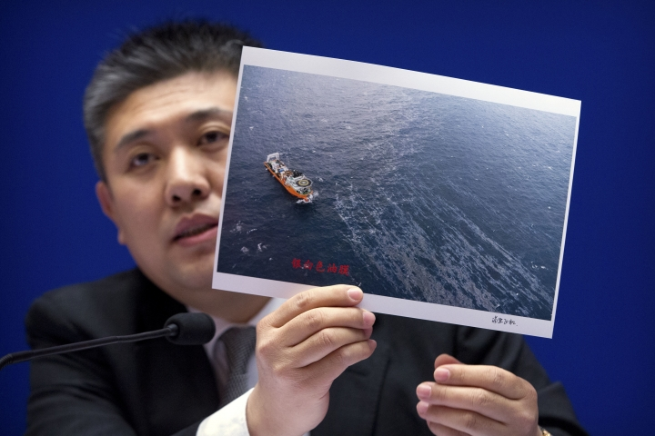 Huo Chuanlin, deputy director of the Department of Ecological and Environment Protection of China's State Oceanic Administration, holds a photo showing a rescue ship and an oil slick during a press conference about the Iranian oil tanker Sanchi, which exploded and sank after a collision in the East China Sea in January, at the Information Office of the Ministry of Transport in Beijing, Thursday, Feb. 1, 2018. Chinese officials say they are still debating whether to try to raise an Iranian oil tanker that sank last month with the loss of all 32 crew members. (AP Photo/Mark Schiefelbein)