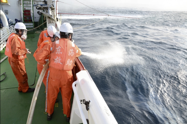 In this undated photo provided by the China Maritime Search and Rescue Center, workers spray an oil slick on the surface of the ocean from the sunken Iranian tanker ship Sanchi in the East China Sea off the coast of China. Chinese officials say they are still debating whether to try to raise an Iranian oil tanker that sank last month with the loss of all 32 crew members. (China Maritime Search and Rescue Center via AP)