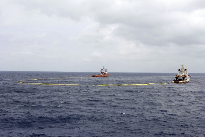 In this undated photo provided by the China Maritime Search and Rescue Center, ships work to contain an oil spill from the sunken Iranian tanker ship Sanchi in the East China Sea off the coast of China. Chinese officials say they are still debating whether to try to raise an Iranian oil tanker that sank last month with the loss of all 32 crew members. (China Maritime Search and Rescue Center via AP)