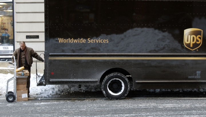 In this Friday, Jan. 5, 2018, photo, a UPS delivery driver loads his cart with packages from his truck, in Boston. UPS Inc. reports earnings Thursday, Feb. 1, 2018. (AP Photo/Bill Sikes)