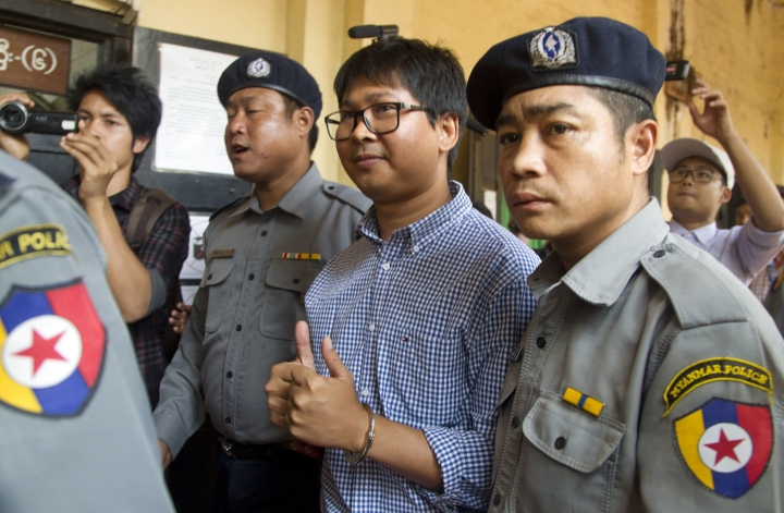Reuters journalist Wa Lone, center, is escorted by police as he returns to court after a break during their trial Thursday, Feb. 1, 2018, outside of Yangon, Myanmar. A lawyer for two Reuters journalists in Myanmar charged with illegally handling government secrets says a court had denied their request to be released on bail. (AP Photo/Thein Zaw)