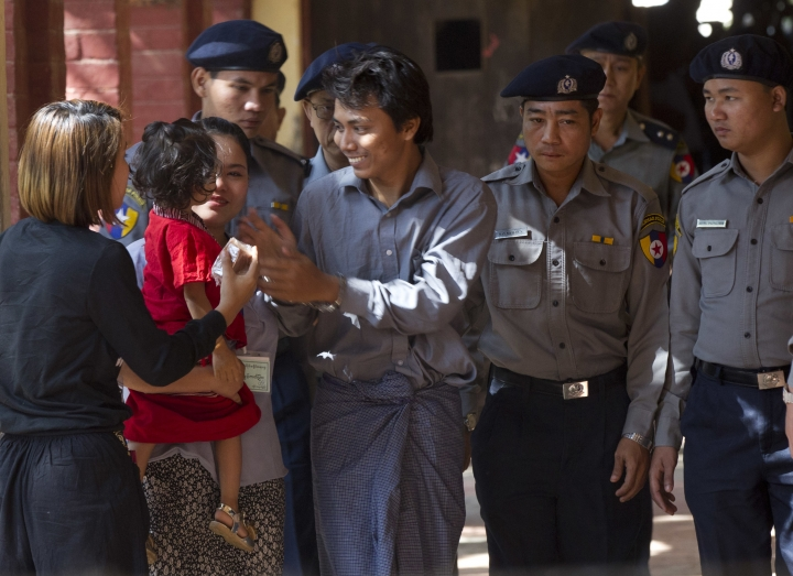"Reuters journalist Kyaw Soe Oo, centre, is welcomed by his wife and daughter upon arrival at the court for their trial Thursday, Feb. 1, 2018, on the outskirts of Yangon, Myanmar. The trial resumes for the two Reuters journalists charged of violating state secrets. Wa Lone and Kyaw Soe Oo were arrested Dec. 12 for acquiring ""important secret papers"" from two police officers who had worked in Rakhine state, where abuses widely blamed on the military have driven more than 630,000 Rohingya Muslims to flee into neighboring Bangladesh.(AP Photo/Thein Zaw)"