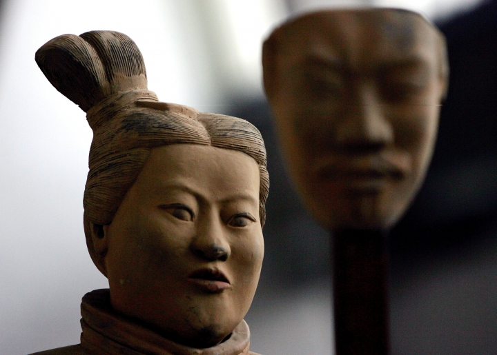 "FILE - In this Feb. 24, 2007 file photo, a female Terracotta soldier statue holds the mask of a man as it stands in the midst of a terracotta army made up entirely of women and children at an art gallery in Beijing. So-called ""female morality schools"" where women are taught to be subservient to men have sparked a storm of criticism in China. Such schools teach women not to fight back if their husbands beat them, avoid career aspirations and to do more housework. (AP Photo/Elizabeth Dalziel, File)"