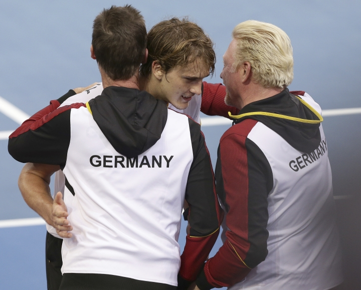 Alexander Zverev of Germany, center, is hugged by Boris Becker, right, after winning his match against Alex de Minaur of Australia, at the Davis Cup World Group first round in Brisbane, Australia, Friday, Feb. 2, 2018. (AP Photo/Tertius Pickard)