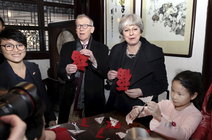 "In this photo released by China's Xinhua News Agency, British Prime Minister Theresa May and her husband Philip hold paper cuttings they made while visiting the Yuyuan Garden in Shanghai, Friday, Feb. 2, 2018. Chinese President Xi Jinping touted the advantages of his ""Belt and Road"" mega-plan for trade and infrastructure links across Asia in a meeting Thursday with British Prime Minister Theresa May, whose government has been slow to endorse the initiative. (Fan Jun/Xinhua via AP)"