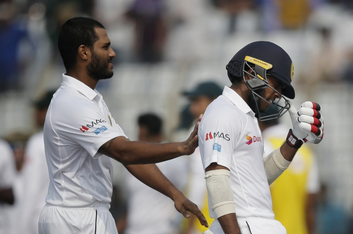Sri Lanka's Roshen Silva, left, consoles his teammate Kusal Mendis, right, as he walks back to the pavilion after his dismissal by Bangladesh's Taijul Islam during the third day of their first test cricket match in Chittagong, Bangladesh, Friday, Feb. 2, 2018. (AP Photo/A.M. Ahad)