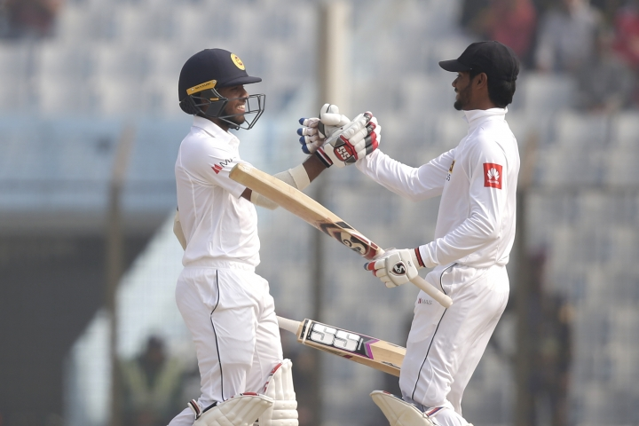Sri Lanka's Dhananjaya de Silva, right, congratulates his teammate Kusal Mendis after scoring hundred runs during the third day of their first test cricket match against Bangladesh in Chittagong, Bangladesh, Friday, Feb. 2, 2018. (AP Photo/A.M. Ahad)