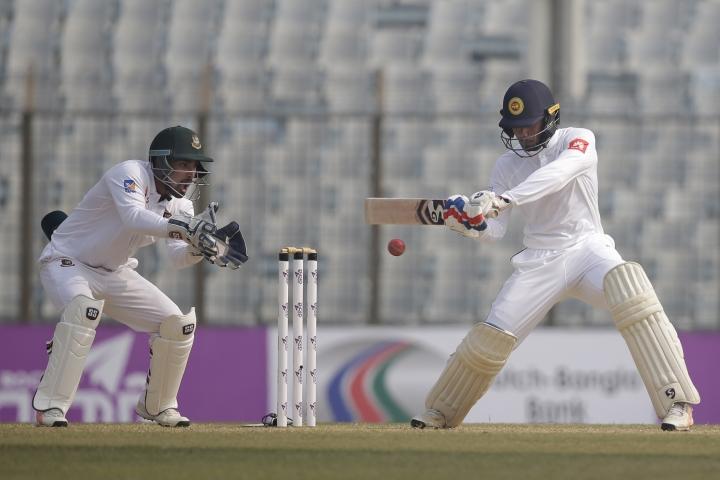 Sri Lanka's Dhananjaya de Silva, right, plays a shot, as Bangladesh's wicketkeeper Liton Das follows the ball during the third day of their first test cricket match in Chittagong, Bangladesh, Friday, Feb. 2, 2018. (AP Photo/A.M. Ahad)