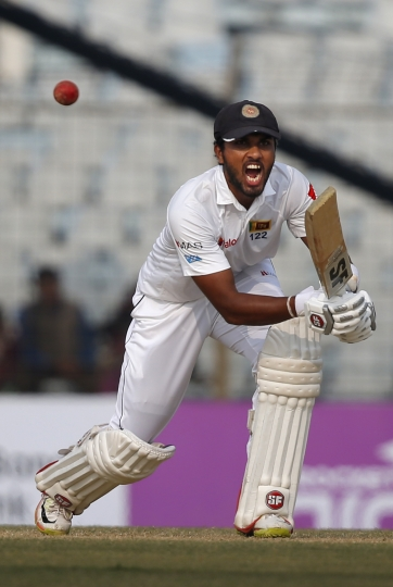 Sri Lanka's captain Dinesh Chandimal plays a shot during the third day of their first test cricket match against Bangladesh in Chittagong, Bangladesh, Friday, Feb. 2, 2018. (AP Photo/A.M. Ahad)